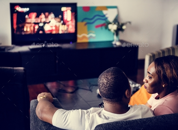 Black spouse watching movie enjoy precious time together - Stock Photo - Images