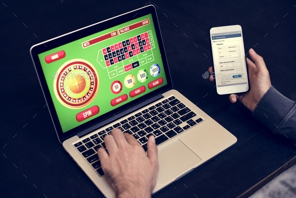 Hand holding credit card playing online gambling - Stock Photo - Images