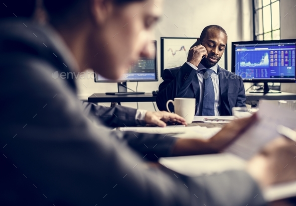 African American businessman making a call in a business meeting - Stock Photo - Images