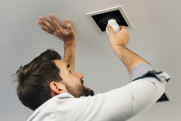 Man changing a light bulb - Stock Photo - Images