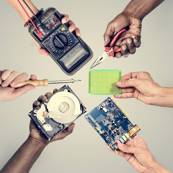 Group of hands holding computer electronics parts on gray background - Stock Photo - Images