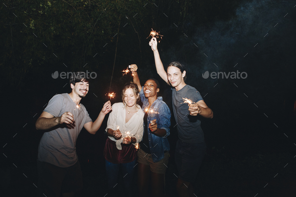 Mixed race friends playing with sparklers celebration and festive party concept - Stock Photo - Images