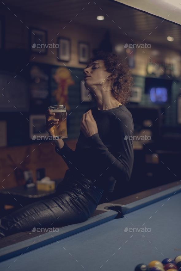 Woman having a beer at a bar - Stock Photo - Images