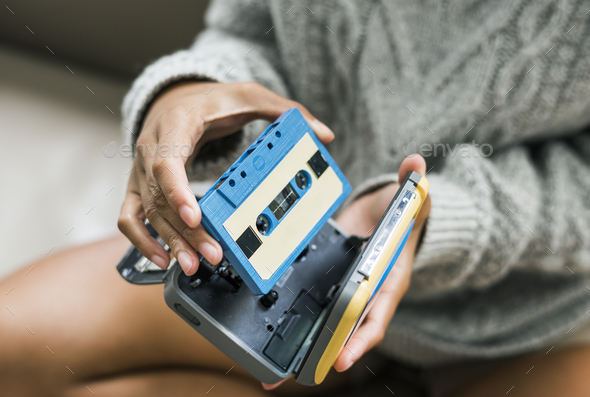 Woman putting a cassette in a cassette player - Stock Photo - Images