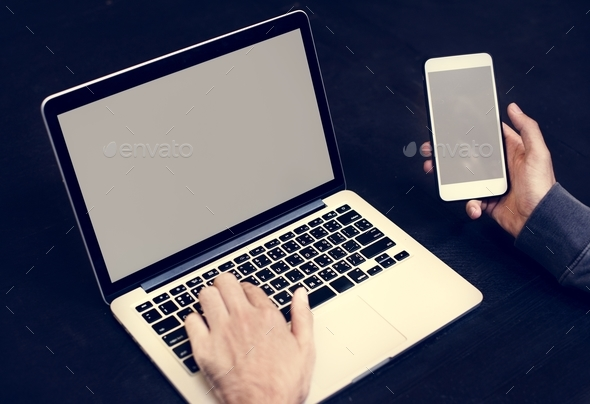 Closeup of hand holding mobile phone with computer laptop background - Stock Photo - Images