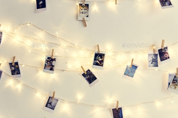 Photos hanging with decoration lights on the white wall - Stock Photo - Images