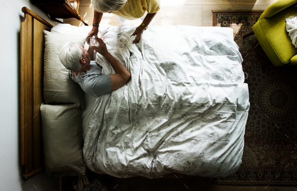 Elderly woman taking care of an elderly man - Stock Photo - Images