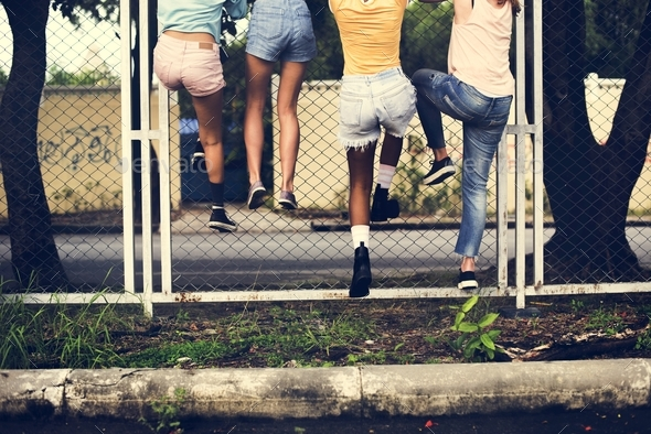Group of women climbing the fence - Stock Photo - Images