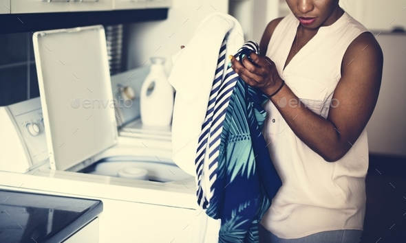 Black woman doing the laundry - Stock Photo - Images