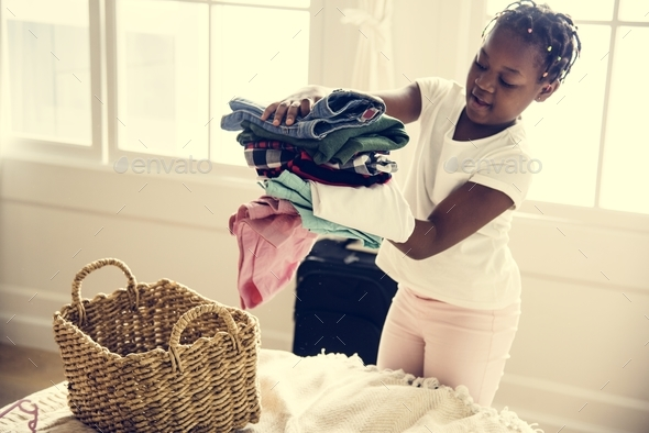 Young teen girl helping with folding the clothes - Stock Photo - Images