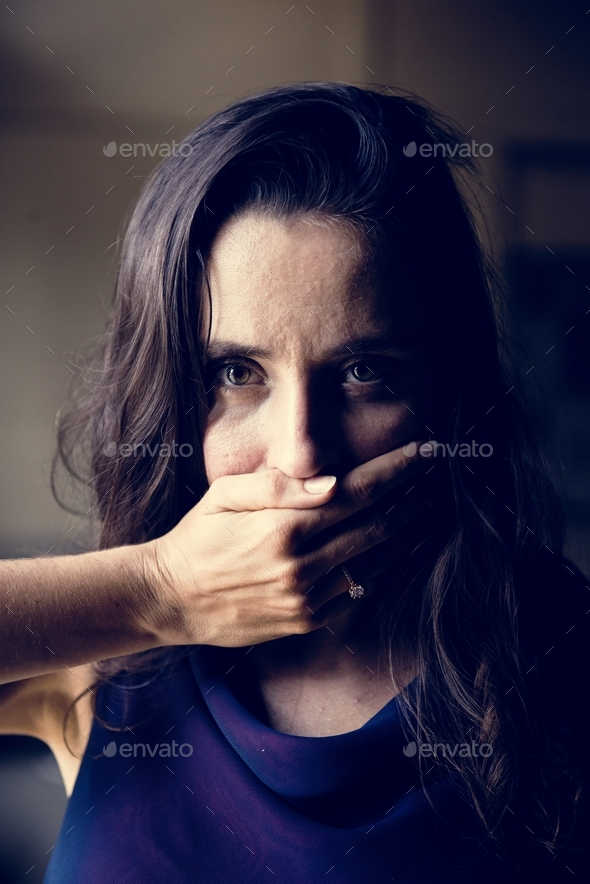 Woman with hand covered over her mouth - Stock Photo - Images