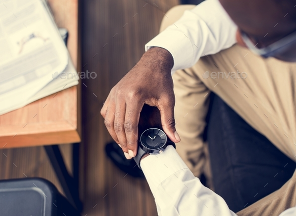 African ethnicity man sitting watching a watch - Stock Photo - Images