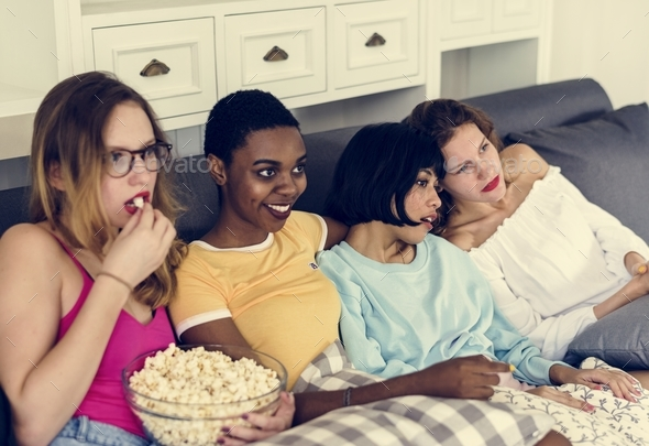 Diverse women eating popcorn together - Stock Photo - Images