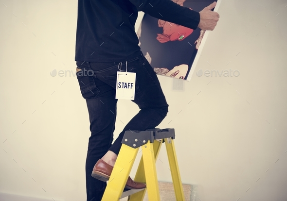 Man taking care of frames in an exhibition - Stock Photo - Images