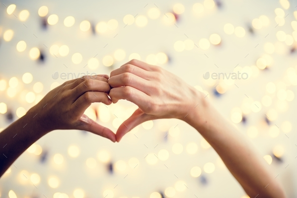 Heart shaped hands with decoration lights as a background - Stock Photo - Images