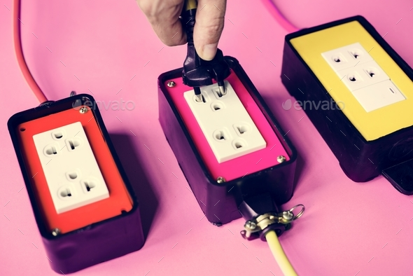 Hand hold electric plug into the outlet - Stock Photo - Images