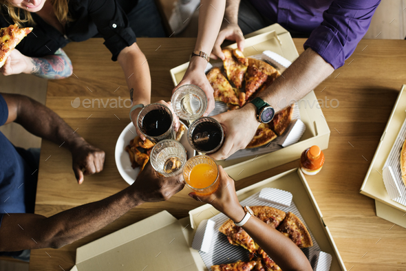 Friends eating pizza together at home - Stock Photo - Images