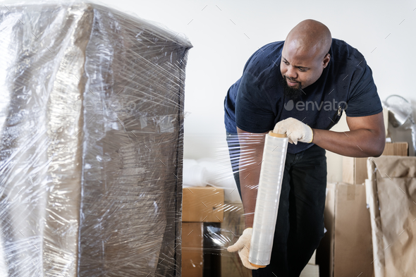 Black man moving furniture - Stock Photo - Images