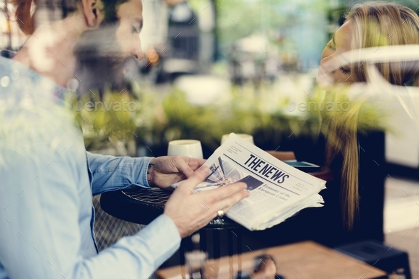 A man with beard showing newspaper to a woman - Stock Photo - Images