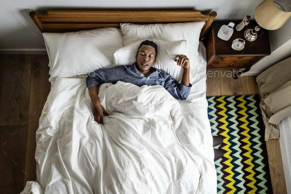 Black man sleeping on bed - Stock Photo - Images