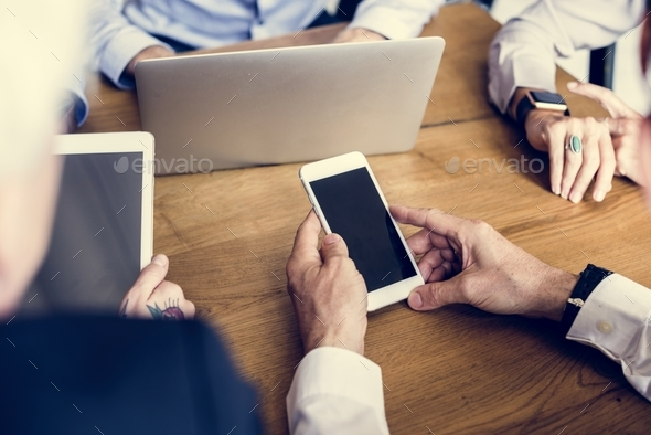Hands holding smartphone in a meeting - Stock Photo - Images