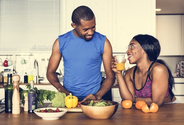 Black couple cooking healthy food in the kitchen - Stock Photo - Images