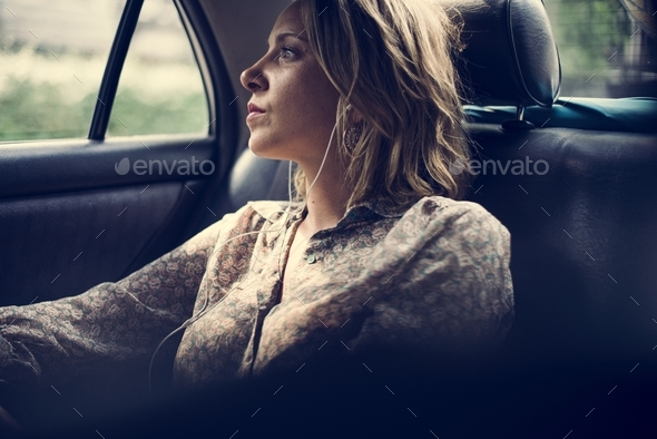 Blond woman sitting in a taxi - Stock Photo - Images