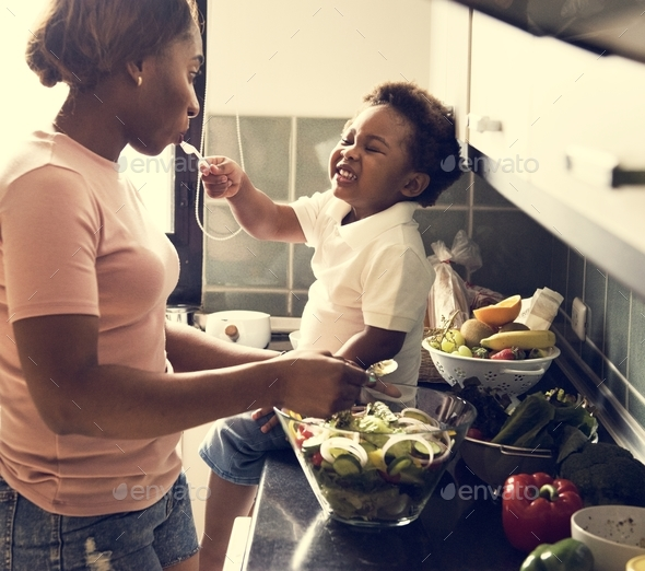 Black kid feeding mother with cooking food in the kitchen - Stock Photo - Images