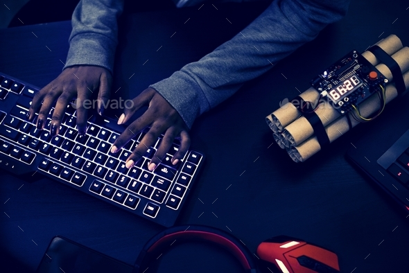 Hacker hacking and bomb on the side - Stock Photo - Images