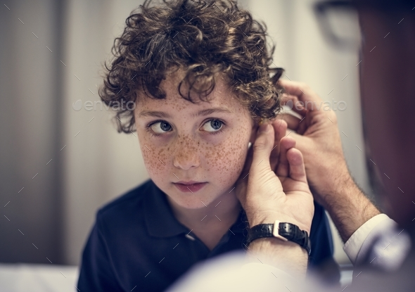 Young having his ears checked - Stock Photo - Images