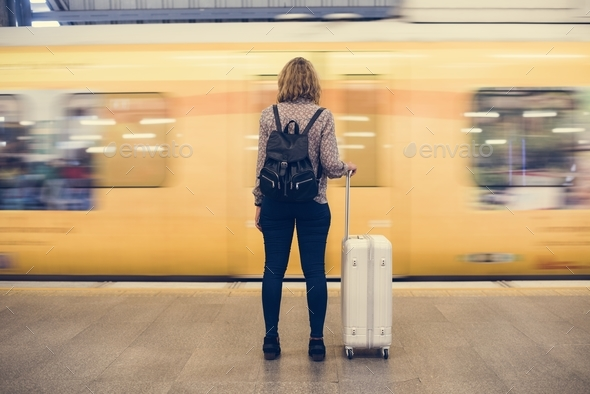 Rear view of a blond woman waiting at the train platform - Stock Photo - Images
