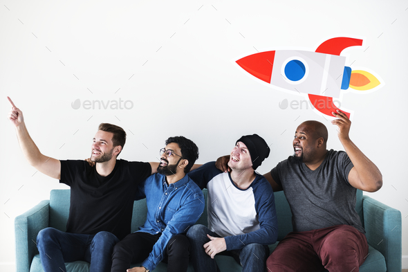 Group of diverse friends sitting on couch with spaceship icon - Stock Photo - Images