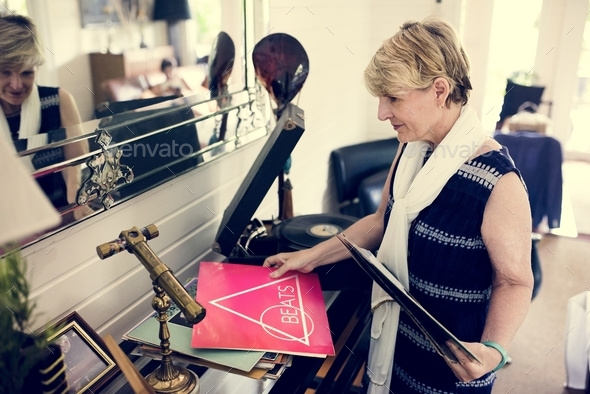 An elderly woman playing a record - Stock Photo - Images