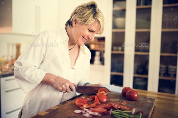 A woman cooking in a kitchen - Stock Photo - Images