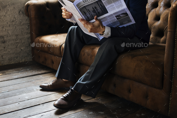 Businessman reading newspaper - Stock Photo - Images
