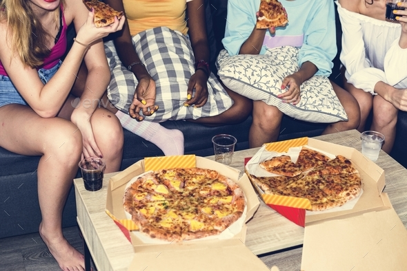 Diverse women sitting on the couch eating pizza together - Stock Photo - Images