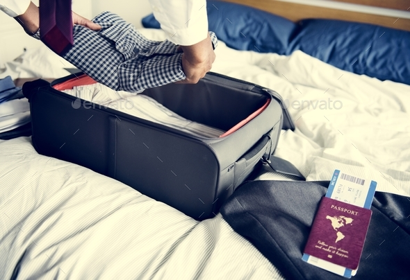 A man preparing his suitcase for travel - Stock Photo - Images