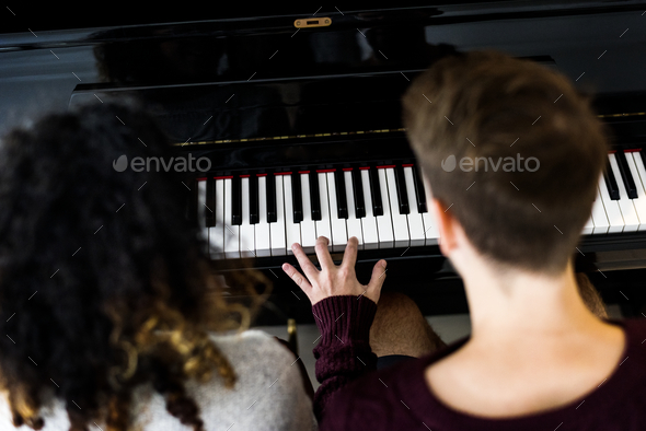 Couple praticing on a piano together - Stock Photo - Images