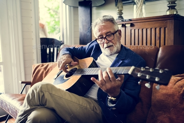 An elderly man is playing guitar - Stock Photo - Images