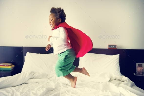 African descent kid jumping on the bed with robe - Stock Photo - Images