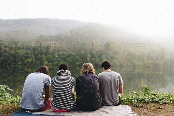 Group of friends relaxing by a lake in the morning - Stock Photo - Images
