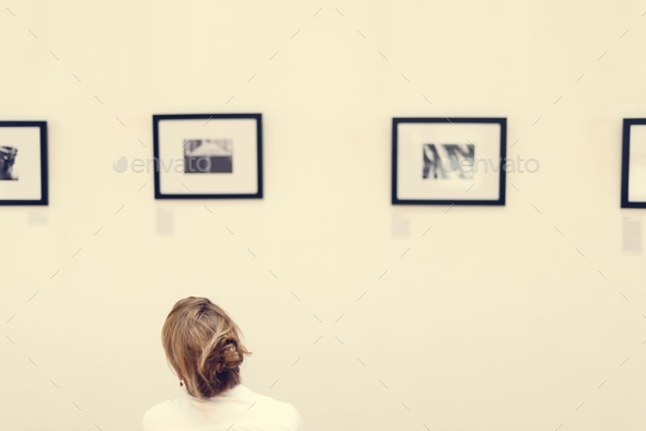 People looking at frames in an exhibition - Stock Photo - Images