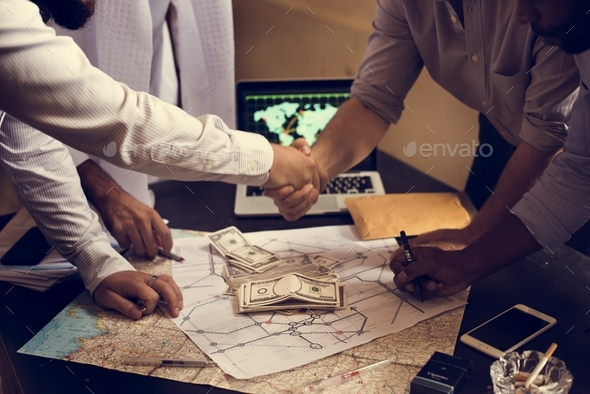 Group of people making agreement handshaking over map and money - Stock Photo - Images