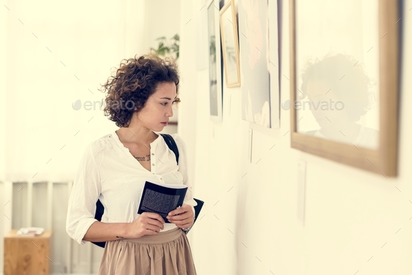 Woman looking at picture frames in an exhibition - Stock Photo - Images