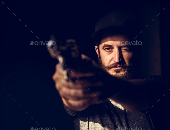 Man holding a gun wth black background - Stock Photo - Images
