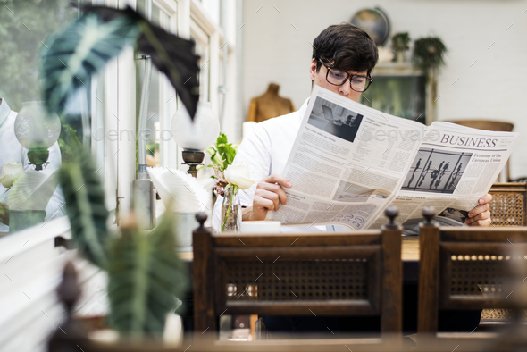 Young man reading newspaper in the morning - Stock Photo - Images