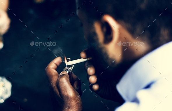 Rear view of man lighting up the cigarette in his mouth - Stock Photo - Images