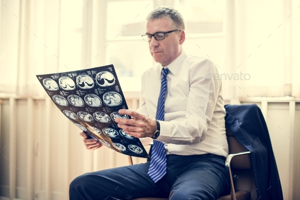 Doctor checking an X-ray result - Stock Photo - Images