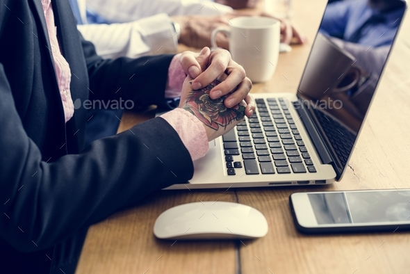Hands with tattoo on laptop and mouse - Stock Photo - Images