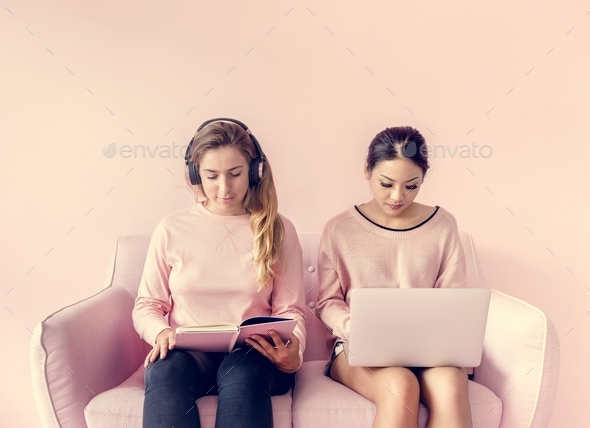 Women sitting together reading book and using computer laptop with pink background - Stock Photo - Images